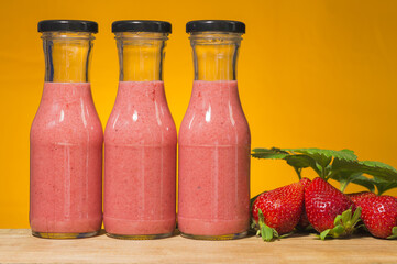 Three bottles with strawberry smoothie on orange background