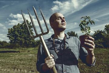 Biobauer mit Forke und Pflanze