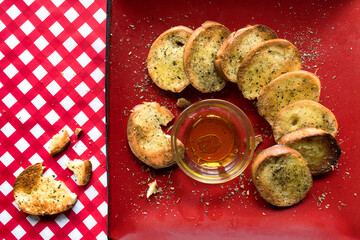 french bread slices with olive oil on red plate and checkerboard tablecloth