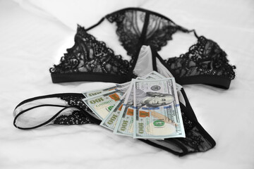 Prostitution concept. Lingerie and money on bed