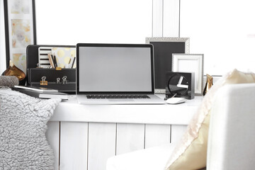 Creative workplace with laptop on windowsill in modern room