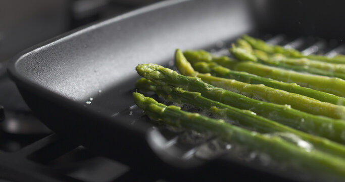 cooking frozen green asparagus on grill pan, wide photo