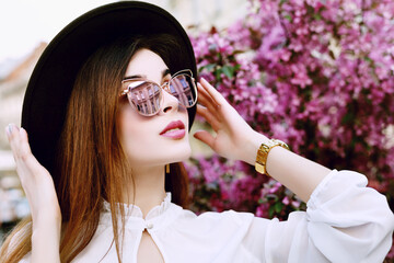 Outdoor close up portrait of beautiful fashionable girl posing near blooming tree with pink flowers. Model wearing stylish sunglasses, black fedora hat. Female fashion concept. Copy, empty space