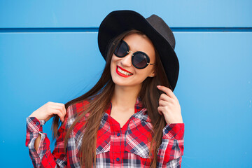 Portrait of beauty fashion smiling hipster girl in hat and sunglasses on blue background