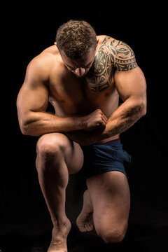 Shirtless muscular man bowing down, kneeling and looking down