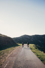Two professional road cyclist team mates athletes ride their bikes into far away diatnce on empty mountain road