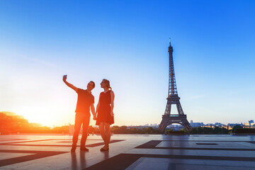 Silhouette of a loving couple taking selfie portrait photo in front of Eiffel Tower, Trocadero, Paris, France