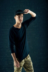 Fashion vogue style portrait of young handsome man in black pullover and cap posing against brick wall background.