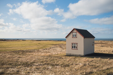A small house to the right on a grassy coastal edge with a big blue sky layered with soft clouds