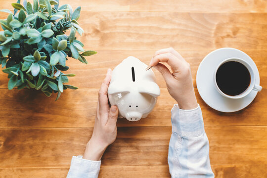 Woman holding a white piggy bank
