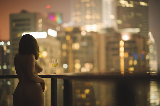 Beautiful naked female on a balcony with a glass of white wine on a background of a night city in Kuala Lumpur. Malaysia