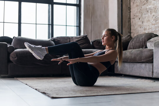 Slim sporty girl doing v-ups abs workout at home