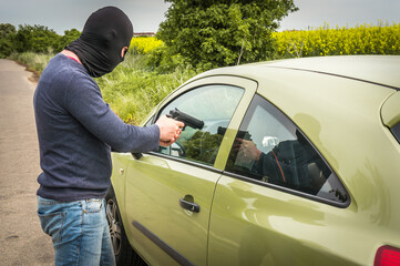 Male thief or terrorist is pointing a pistol on the driver