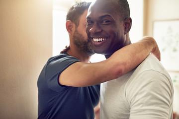 Happy homosexual man embracing with unrecognizable partner