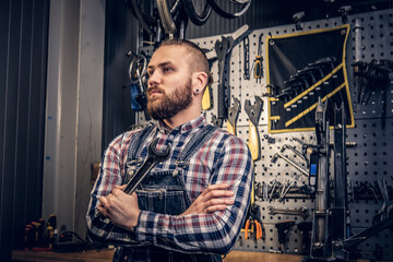Portrait of bearded bicycle mechanic with crossed arms.