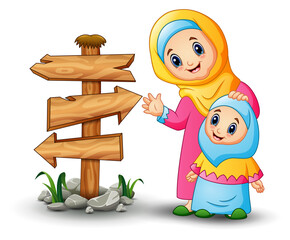 A muslim women hold her daughter head with blank wood arrow sign