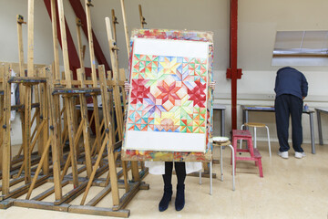 a high school student holding up a painting made at creative lessons