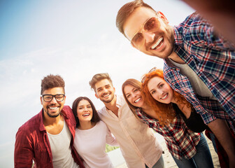 Group of young people taking a selfie outdoors on the beach, having fun