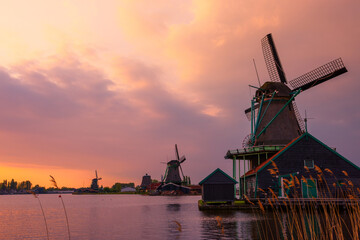 Traditional Dutch windmills on the canal bank at warm sunset in Netherlands near Amsterdam