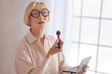 Modern grandmother using powder rouge