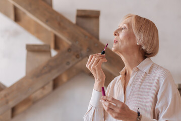 Fashionable female putting up her lipstick
