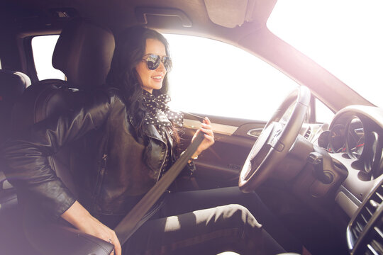 Brunette in sunglasses woman fastens expensive car