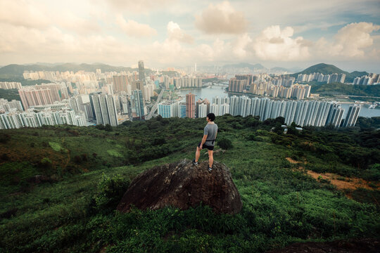 man traveler standing on top of cliff in mountain and enjoying view of Hong Kong