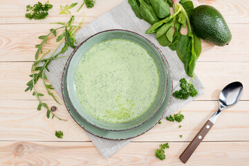 Top view of green creamy soup with fresh healthy ingredients on table