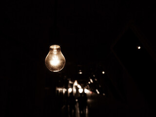 Hanging light bulb in darkness