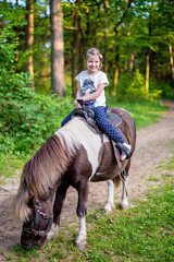 Happy smiling little girl on a pony in the forest. Vertical