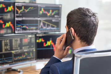 Over the shoulder view of and stock broker trading online while accepting orders by phone. Multiple computer screens ful of charts and data analyses in background.