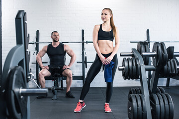 Smiling muscular man looking at sporty woman holding towel and bottle of water in gym