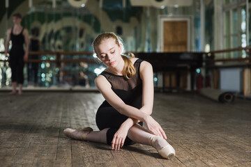 Young ballet dancer practicing in class. Ballerina doing exercises. Girl stretches herself in the dancing hall.