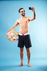 Happy shirtless guy holding beach ball and making selfie