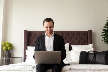 Happy man wearing business suit sitting on bed with luggage and working on laptop. Businessman ready to travel orders airline tickets online. Entrepreneur searching in Internet vacation travel tour