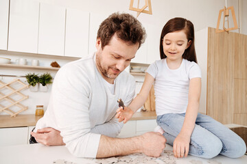 Single-parent family spending time together while doing puzzle