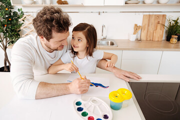Happy father painting together with his daughter