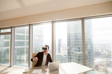 Businessman in VR headset interacts with objects in virtual reality, sitting at desk in office with modern cityscape outside the window. Man, company CEO working in digital simulation with gestures