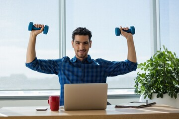 Portrait of executive exercising with dumbbells while working on laptop