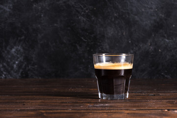 glass of freshly made dark coffee on wooden tabletop