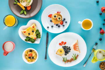 top view of food styling breakfast with various dishes on blue background