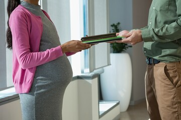 Mid section of pregnant woman giving file to colleague
