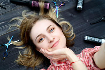 Selfie photo of  happy smiling young woman in plaid shirt with hairdresser tools among her