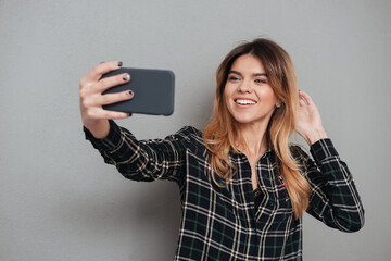 Smiling lovely girl making a selfie with mobile phone
