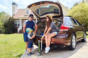 Family sits in cars trunk near house. Mother, father, son.