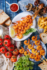 Variety of BBQ snack lunch. Plates grilled spicy king prawn kebabs, mushrooms skewers, bread, french fries potatoes, tomatoes with sauces and greens over blue wooden background. Flat lay