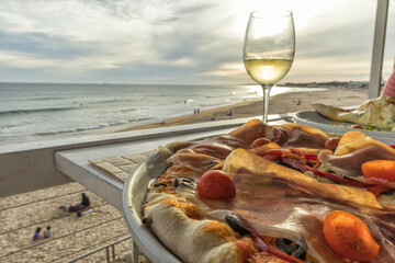 Homemade pizza with ham tomato olives and peppers with glass of white wine and the beach at sunset in background