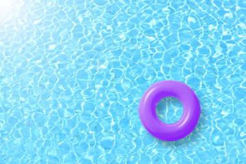 purple swimming pool ring float in blue water and sun bright. concept color summer.