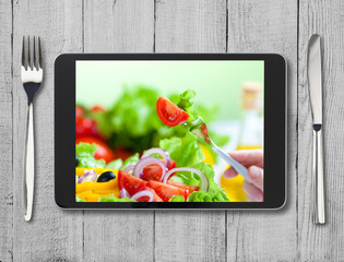 black tablet pc with healthy food on screen and wooden table