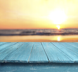 blue table top against blurred sunset beach background